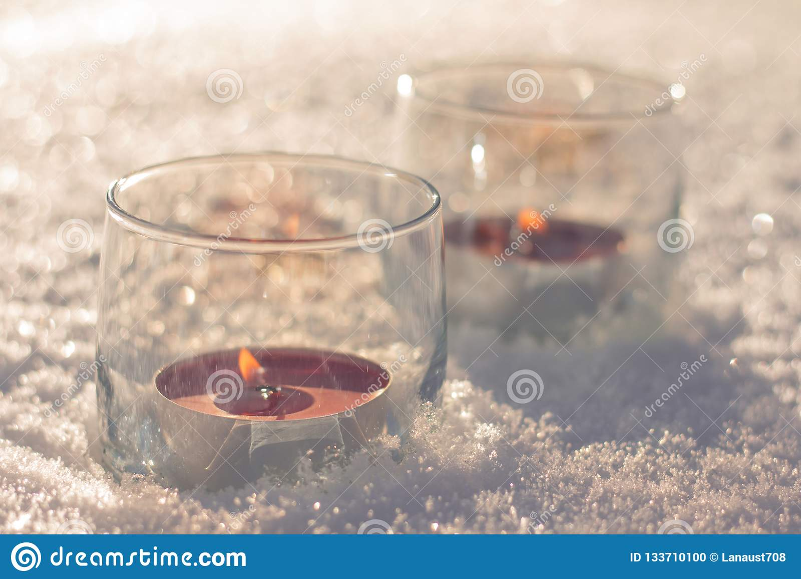 Deux bougies dans les verres sur la neige