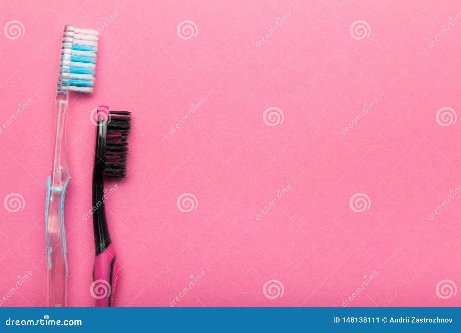 Deux brosses à dents hygiéniques sur un fond rose Copiez l espace
