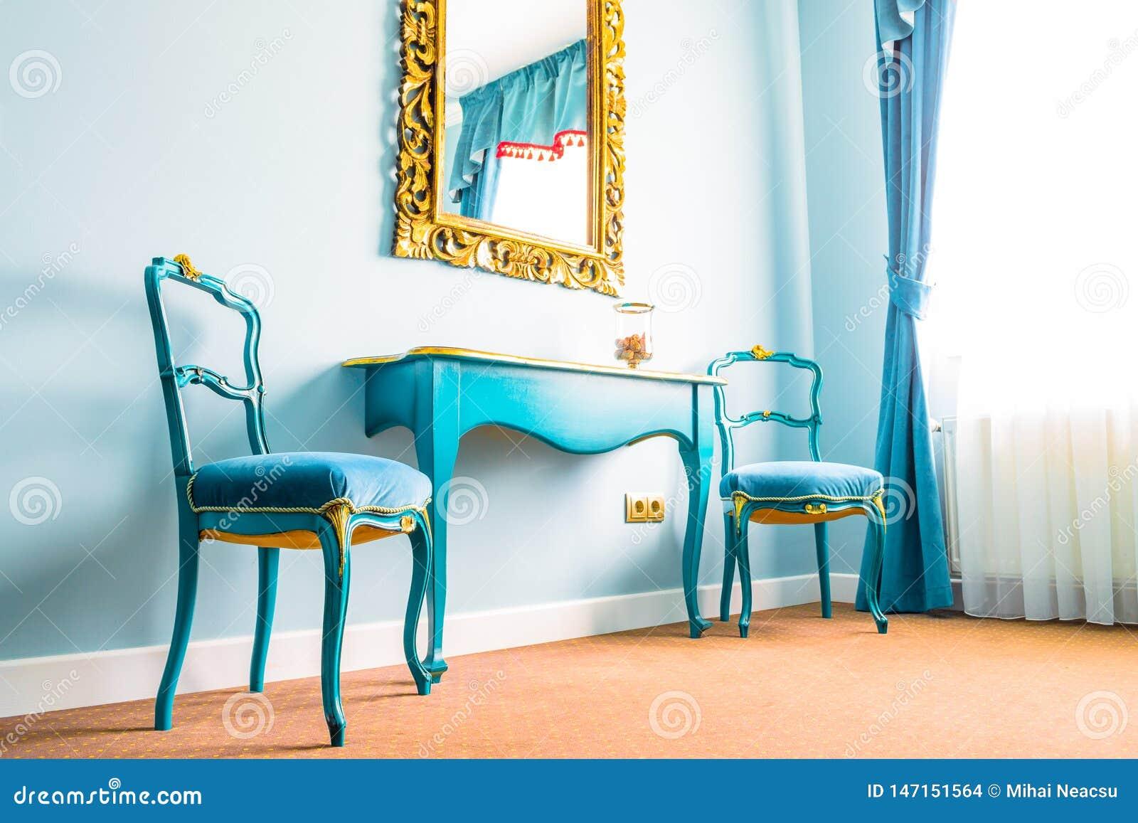 Décorer Son Mur Avec Des Photos deux chaises bleues de cru et une table en bois, à côté d'un