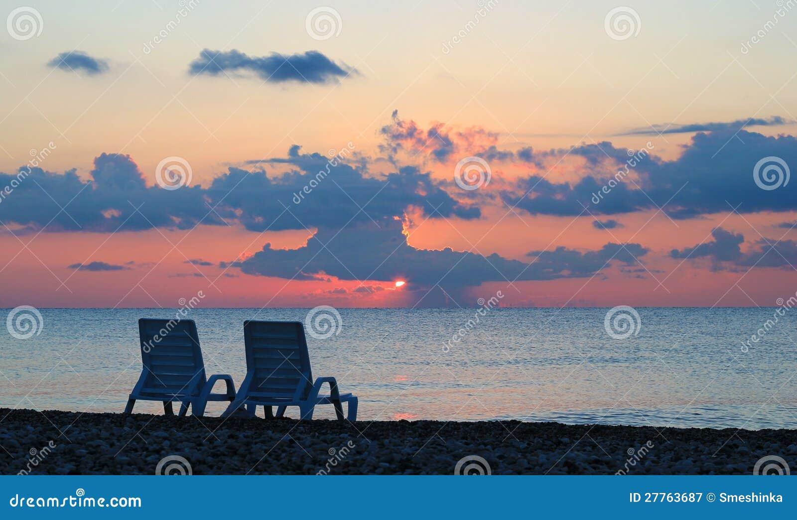 Deux chaises longues sur la plage au beau lever de soleil
