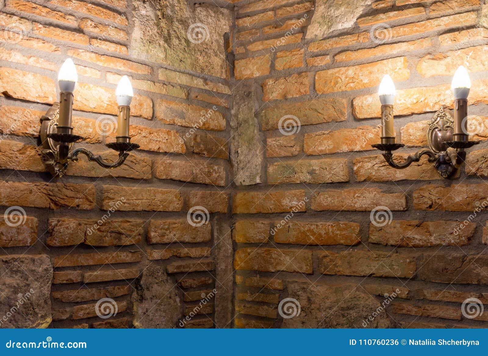 Deux chandeliers avec des lampes dans le coin du mur de briques dans le bâtiment antique Intérieur médiéval Vieille maison de pie