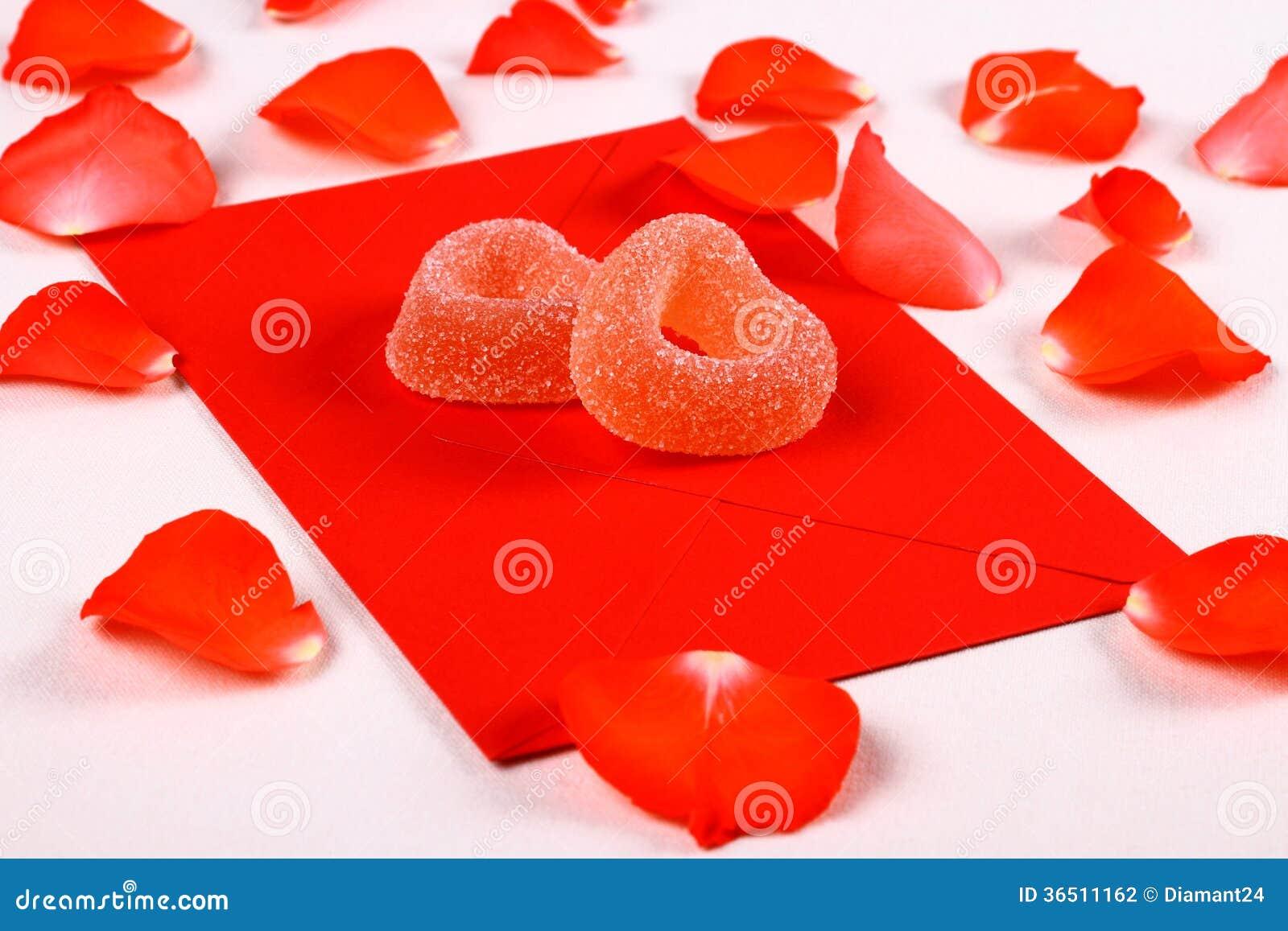 Deux coeurs des sucreries de sucre sur l enveloppe et les pétales rouges
