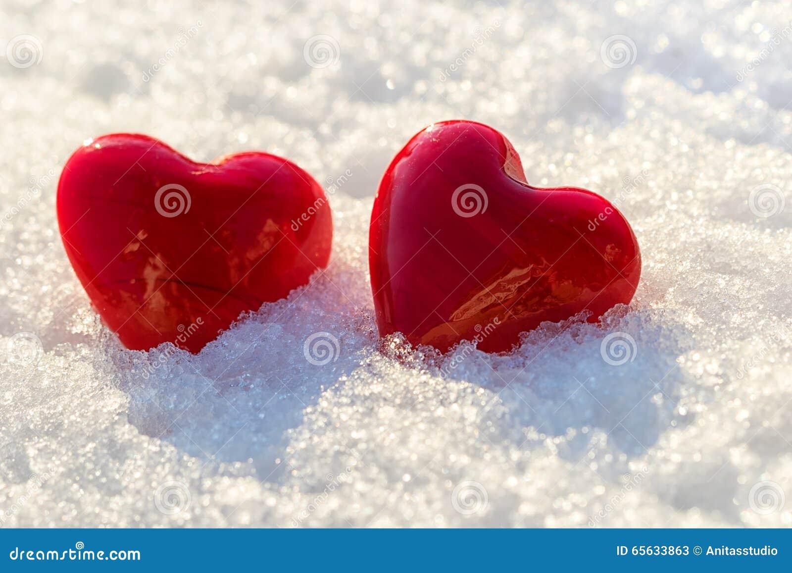 Deux coeurs rouges sur la glace ont mouillé la neige, foyer sélectif