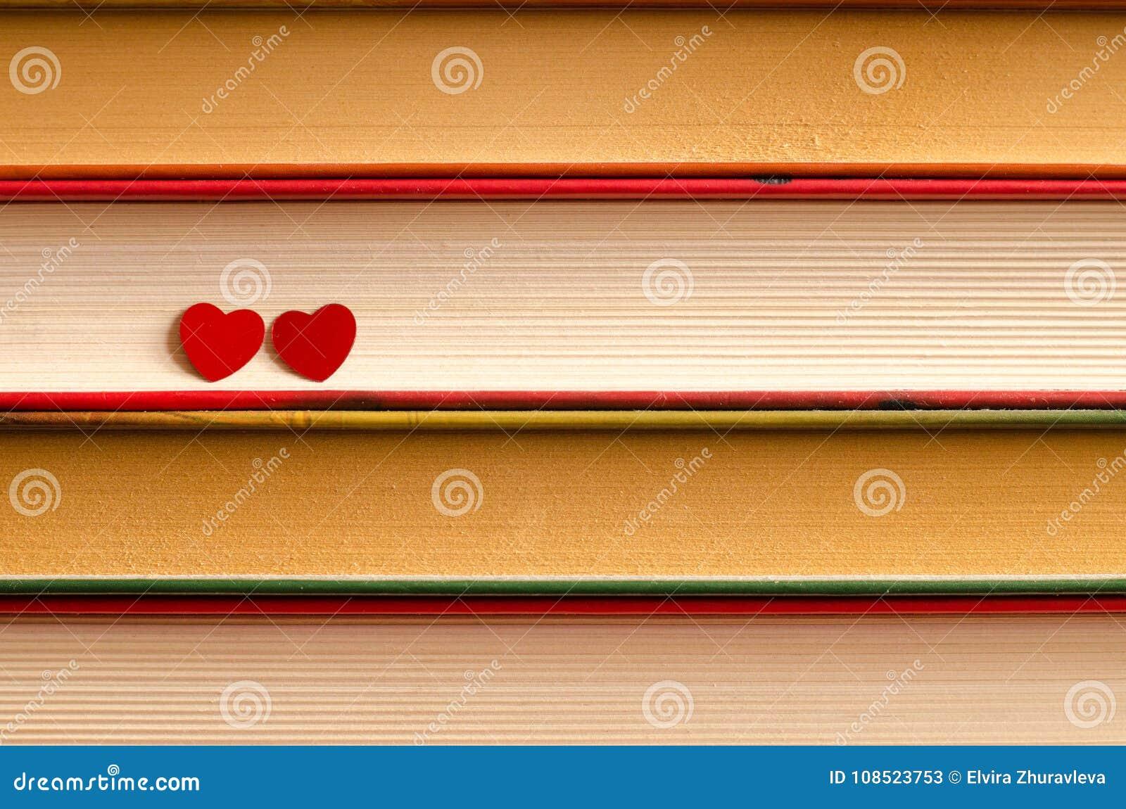 Deux coeurs sur une pile de livres se ferment