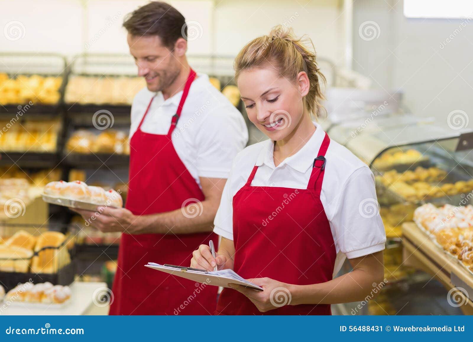 Deux collègues de sourire écrivant sur le bloc-notes