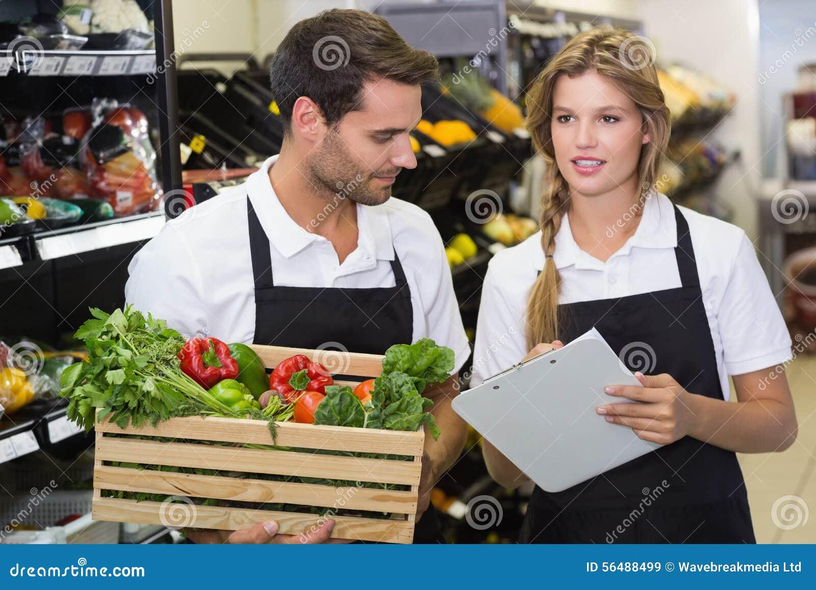 Deux collègues tenant une boîte avec les légumes frais et écrivant sur le bloc-notes