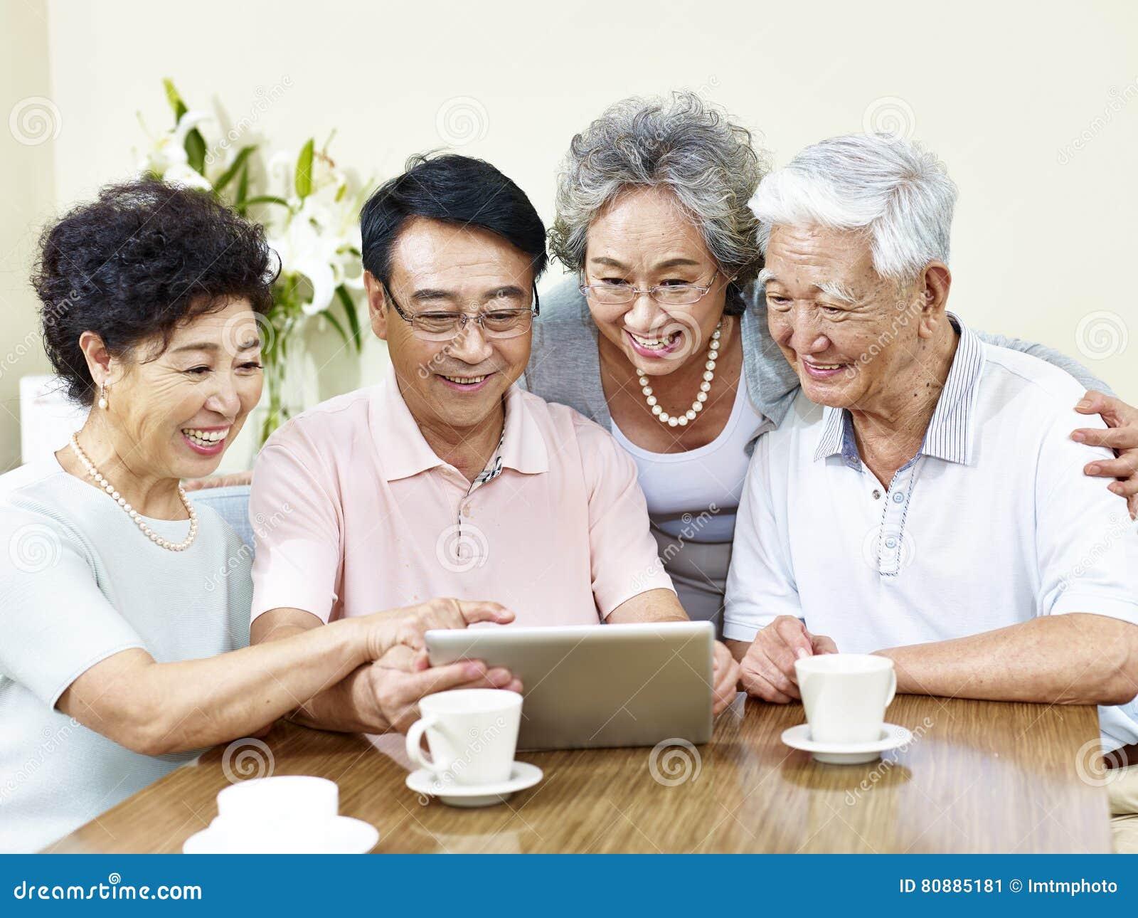 Deux couples asiatiques supérieurs utilisant la tablette