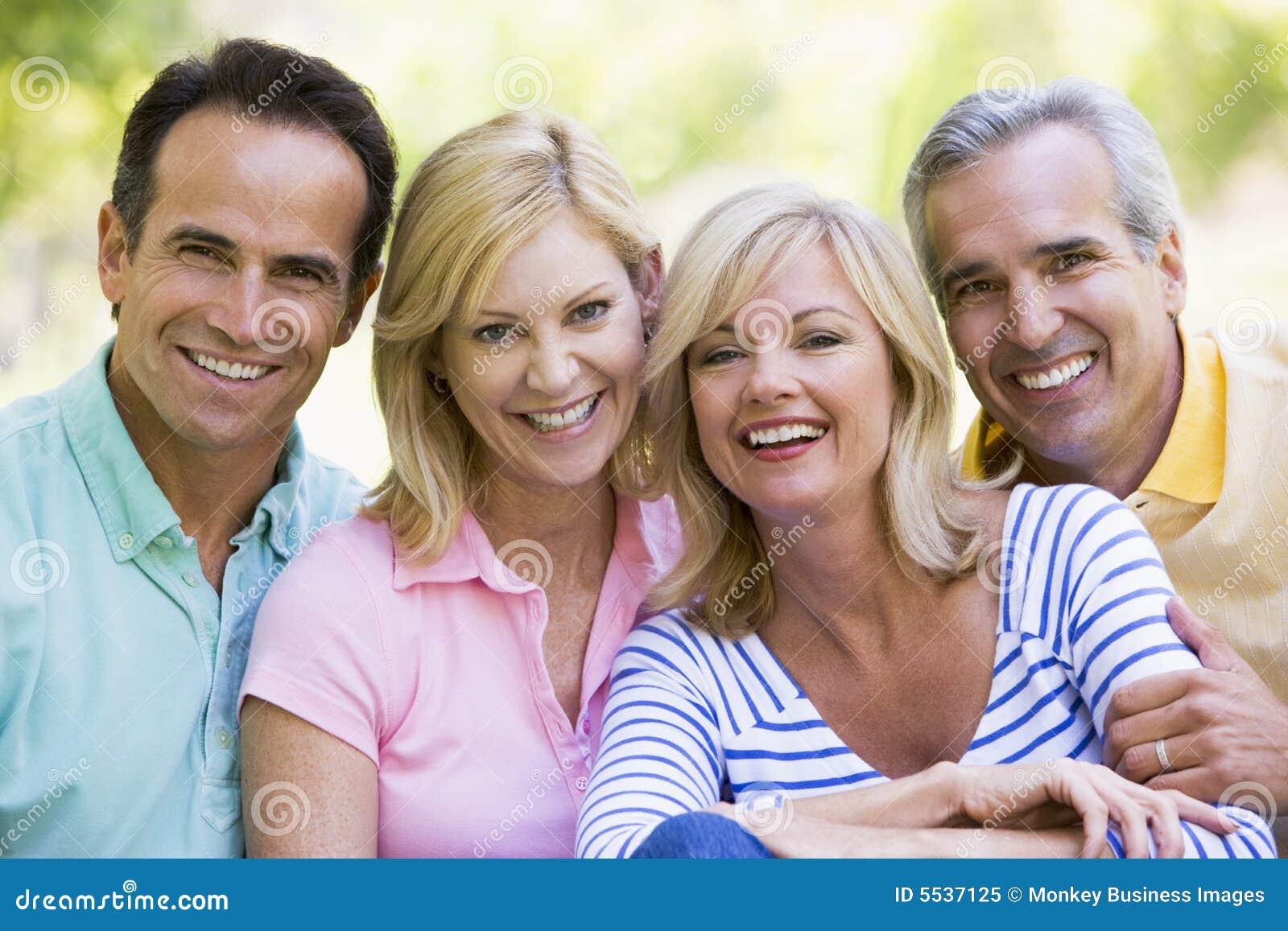 Deux couples souriant à l extérieur