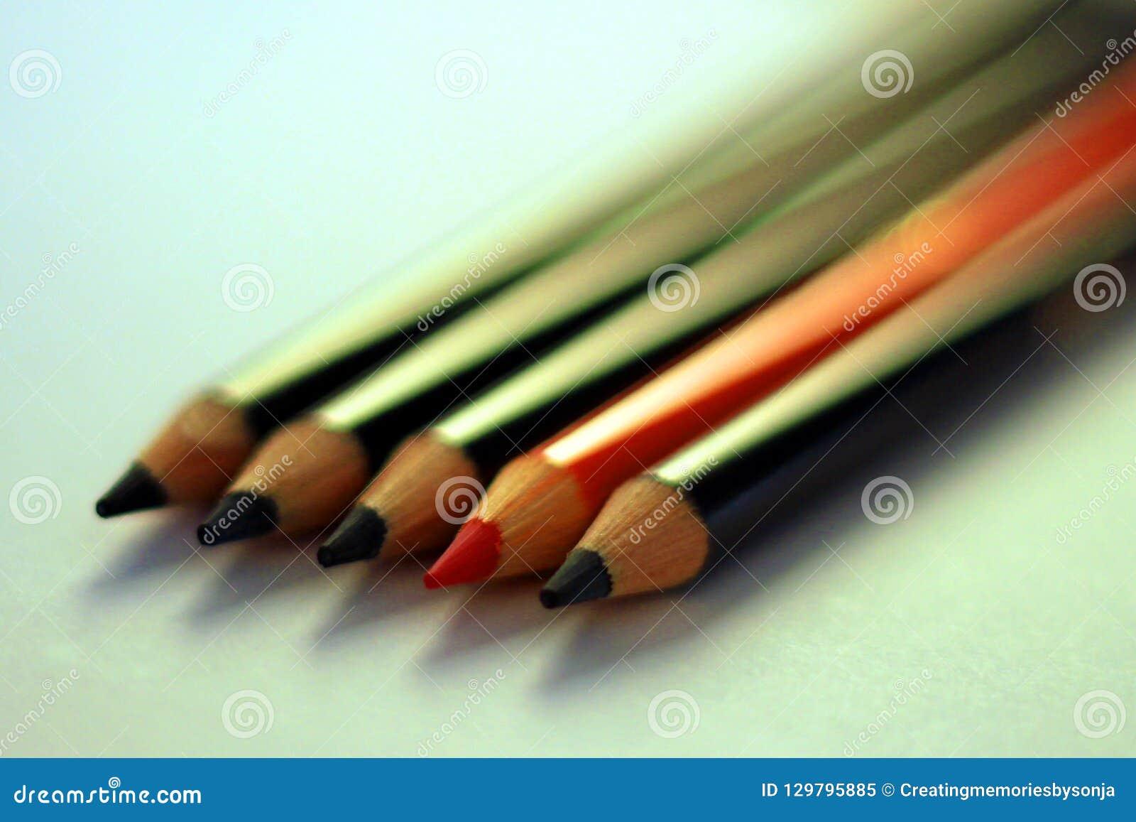 Deux crayons oranges entre les crayons noirs