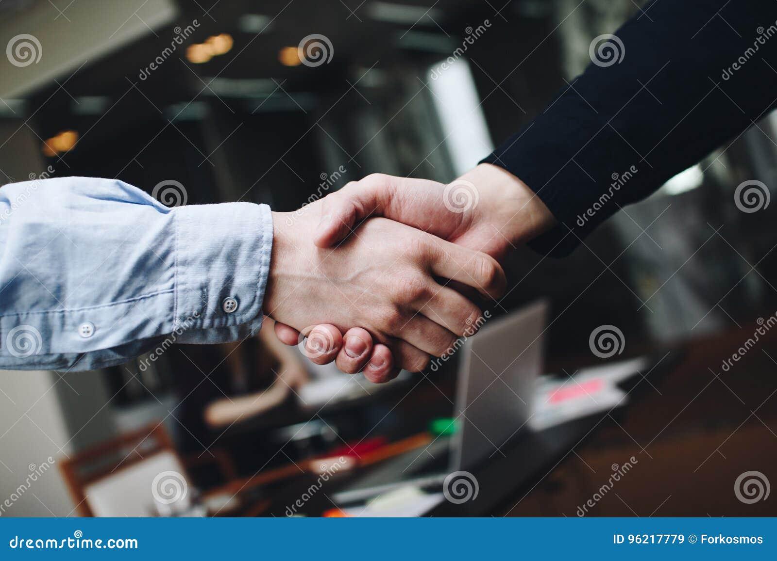 Deux directeurs dans les vêtements décontractés dans des poignées de main de lieu de réunion après conclusion du compromis
