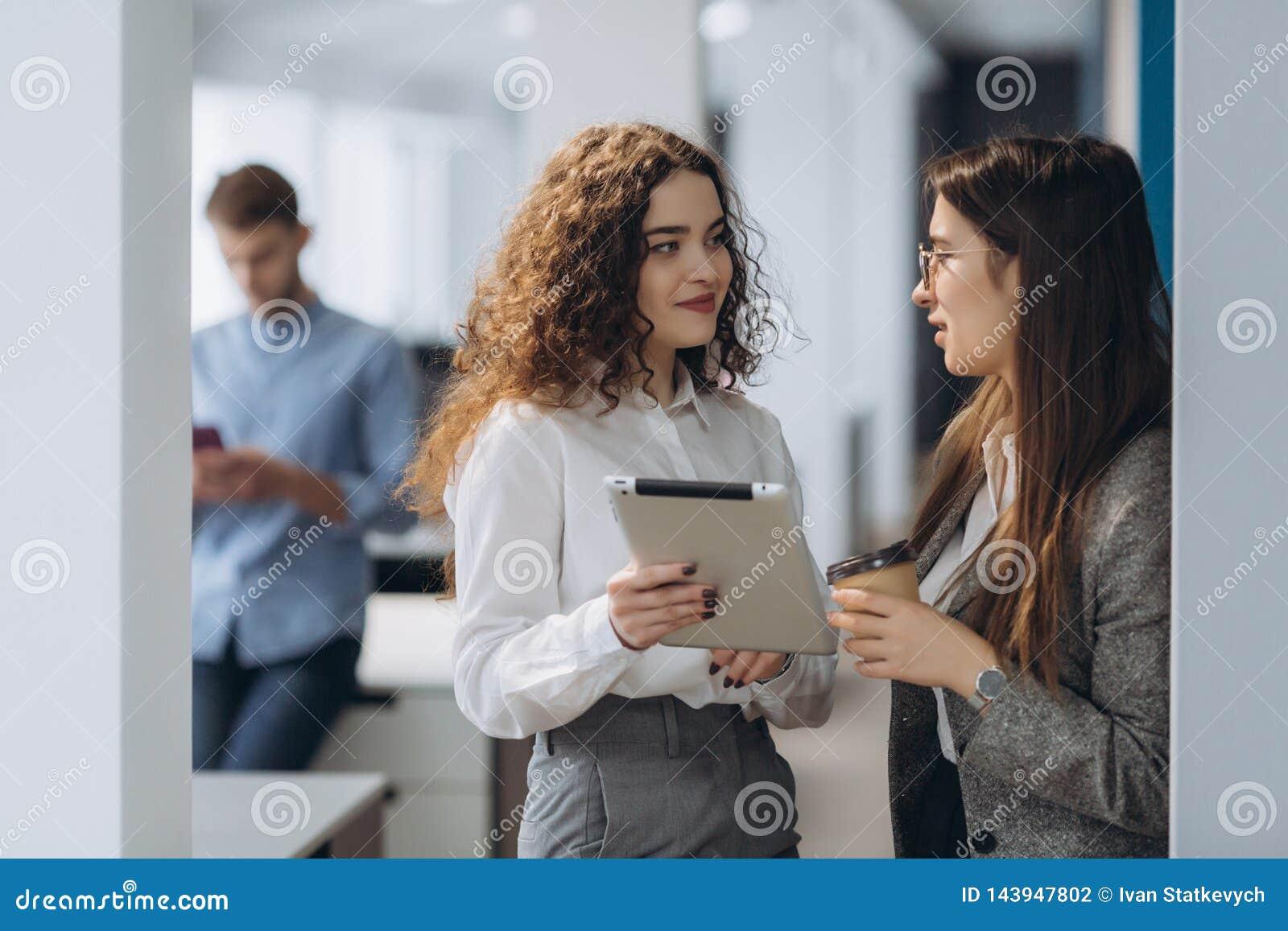 Deux directeurs généraux féminins discutant des idées du projet sur le comprimé numérique tout en marchant vers le bas dans