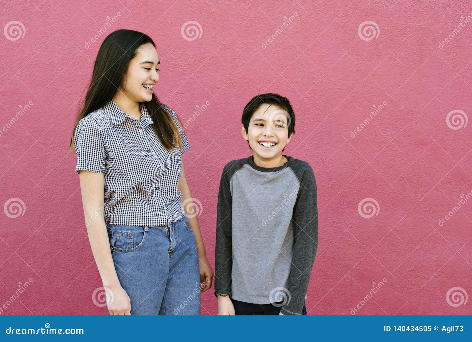 Deux enfants d enfant de mêmes parents se tiennent contre un mur rose riant et ayant l amusement