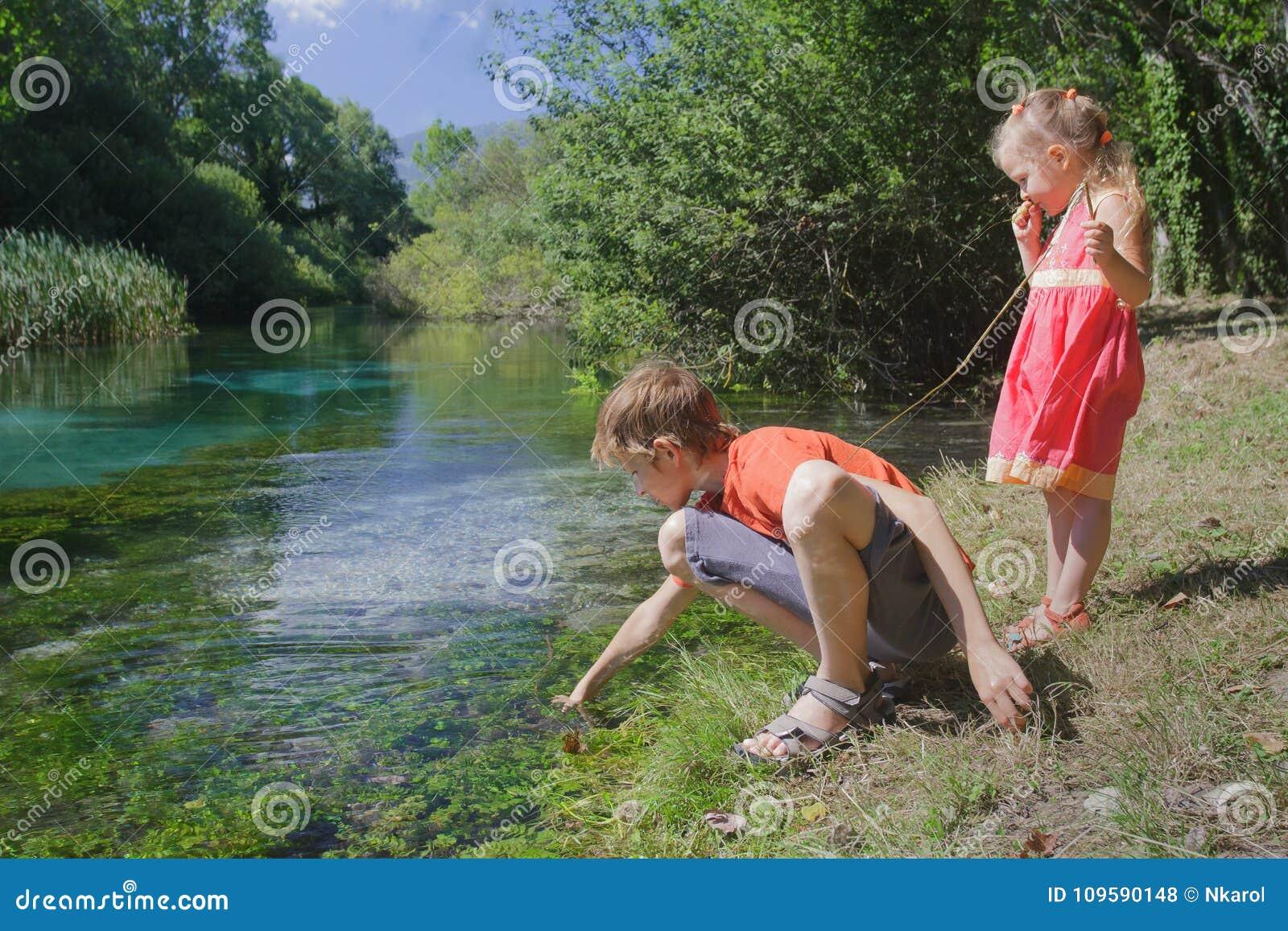 Deux enfants de mêmes parents jouant sur la berge de Tirino d Italien avec le bâton
