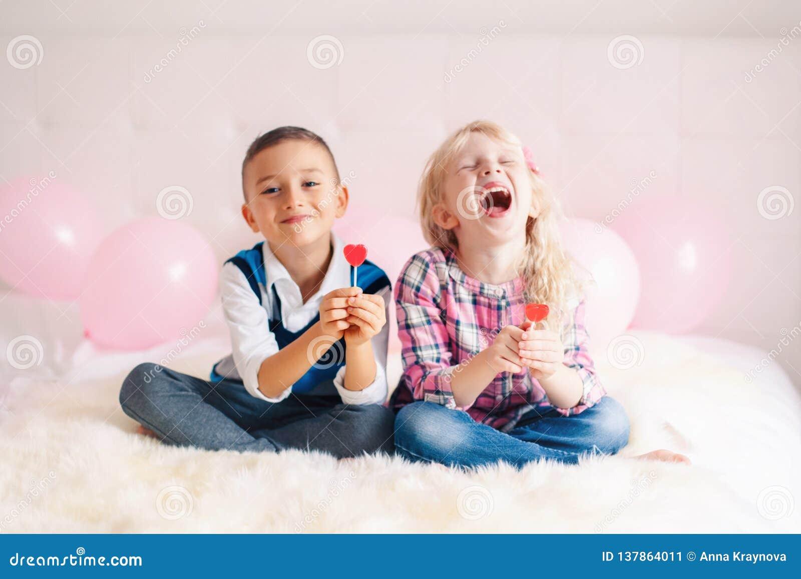 Deux enfants drôles adorables mignons caucasiens blancs heureux mangeant les lucettes en forme de coeur