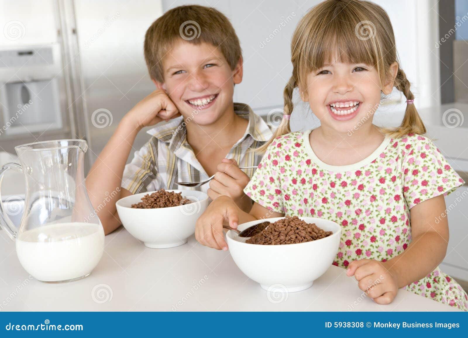 Deux enfants en bas âge dans la cuisine mangeant de la céréale