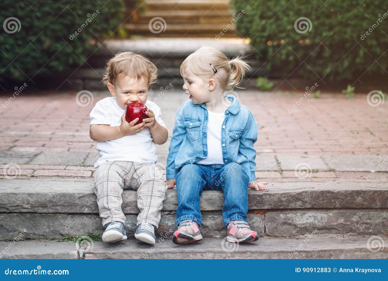 Deux enfants en bas âge drôles adorables mignons caucasiens blancs d enfants reposant partager ensemble mangeant de la nourriture