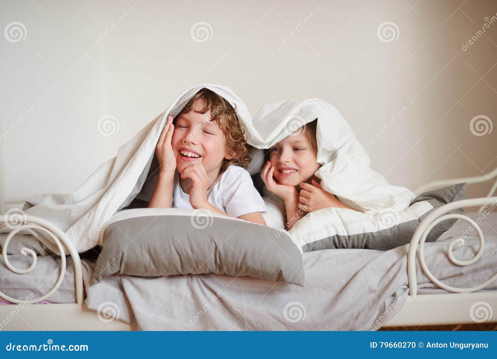 deux enfants fr re et soeur squirmy sur le lit dans la chambre coucher photo stock image. Black Bedroom Furniture Sets. Home Design Ideas