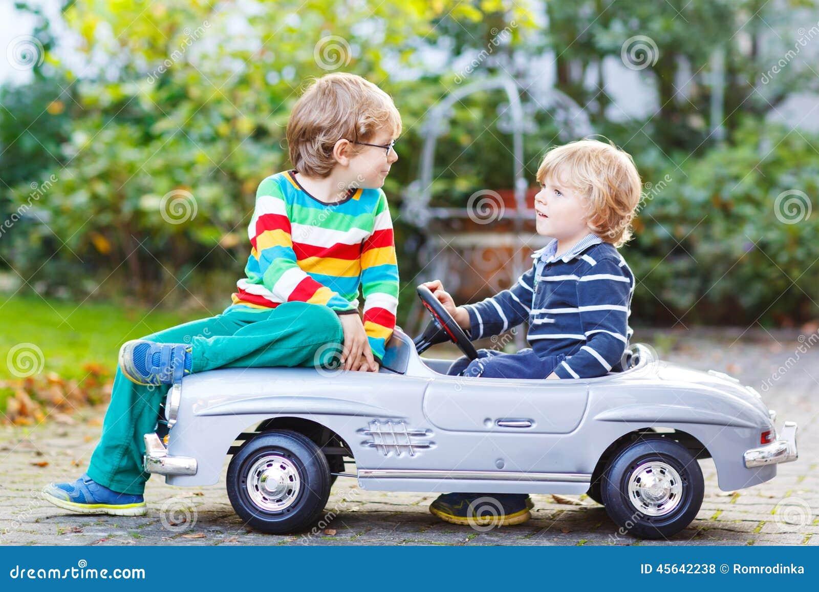 deux enfants heureux jouant avec la grande vieille voiture de jouet en t font du jardinage ou. Black Bedroom Furniture Sets. Home Design Ideas
