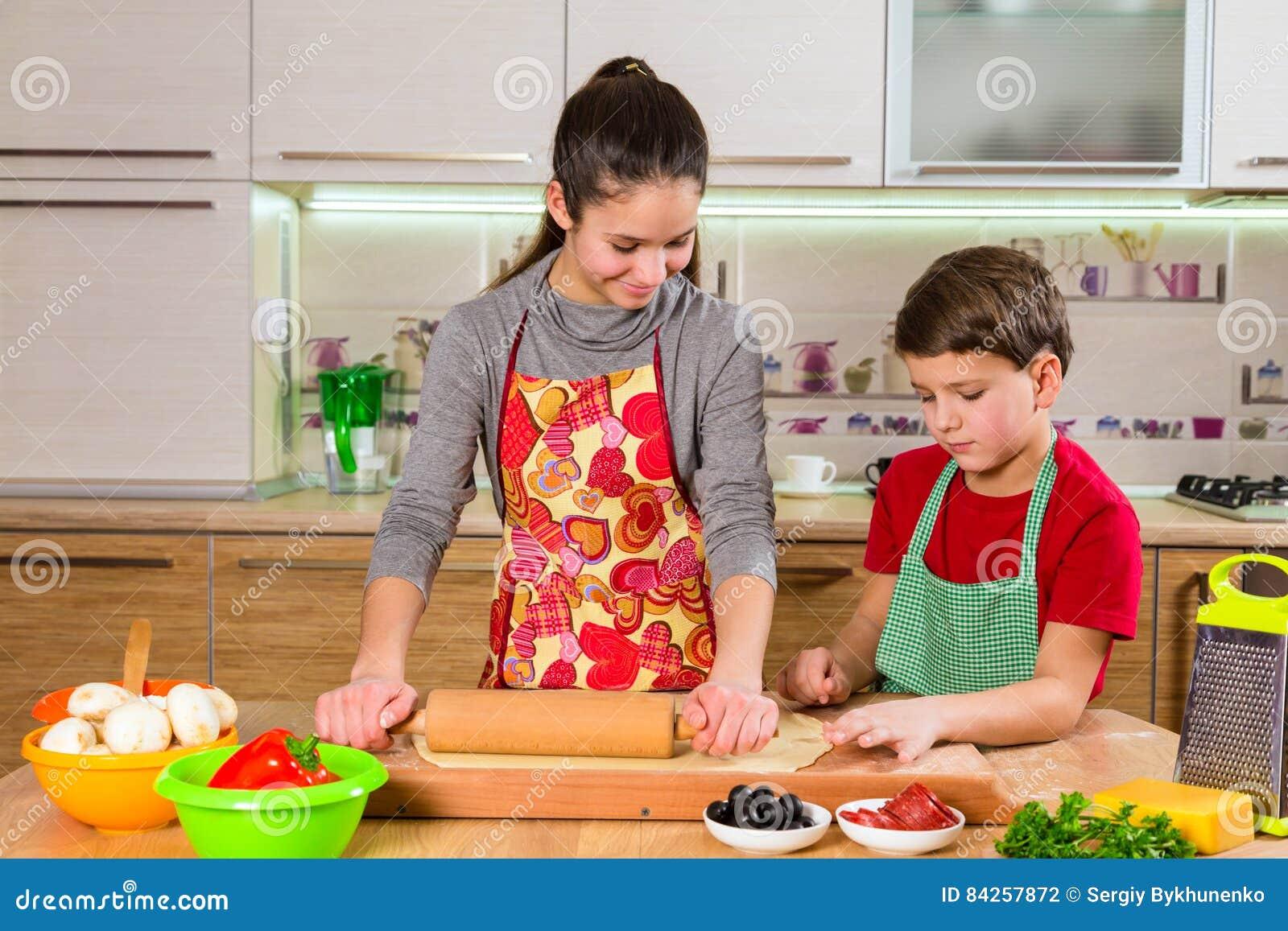 Deux enfants malaxant la pâte, faisant la pizza