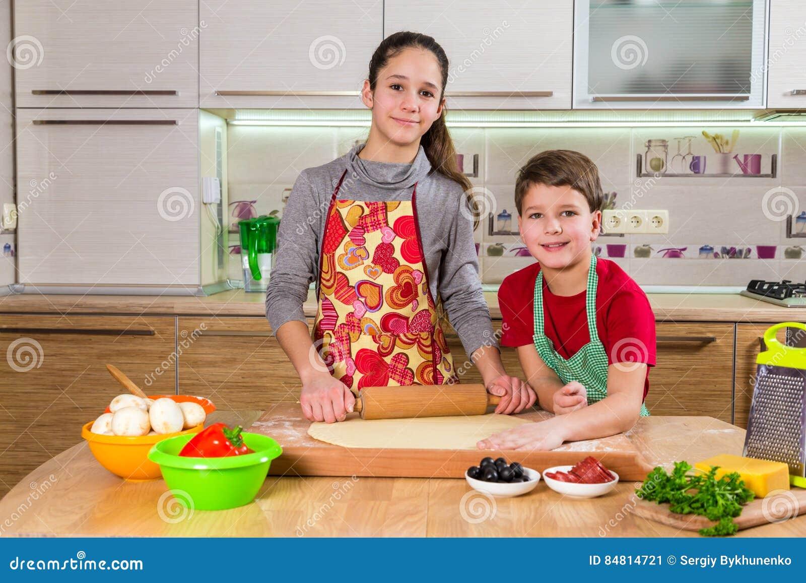 Deux enfants malaxant la pâte pour faire la pizza
