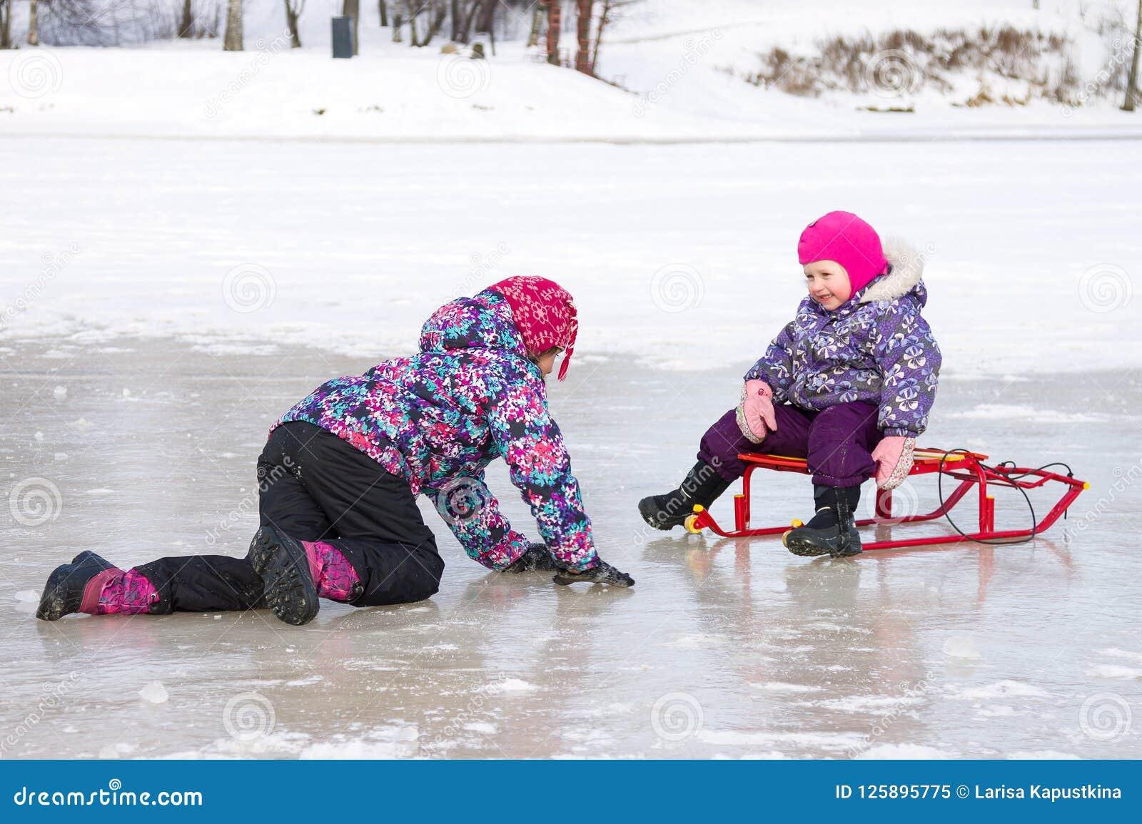 Deux enfants ont l amusement se reposant ensemble sur la glace et jouant avec un traîneau de neige un jour clair d hiver
