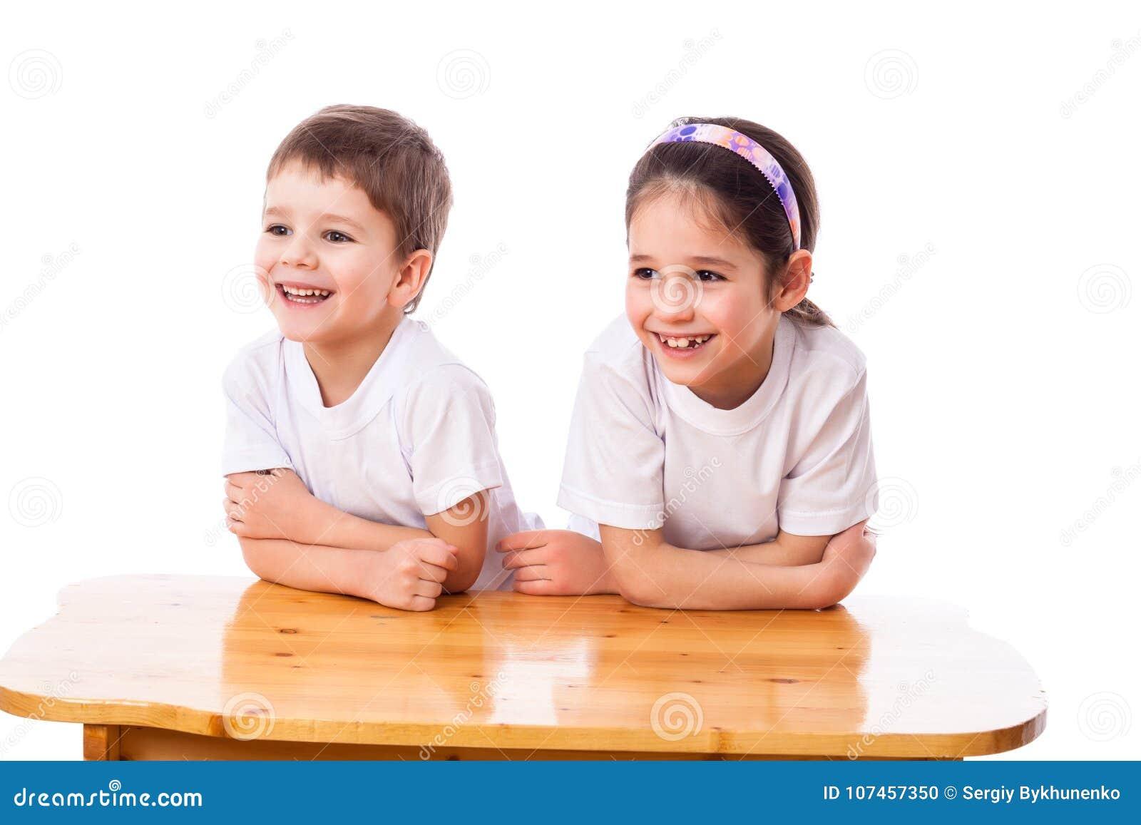 Deux enfants riants au bureau regardant de côté