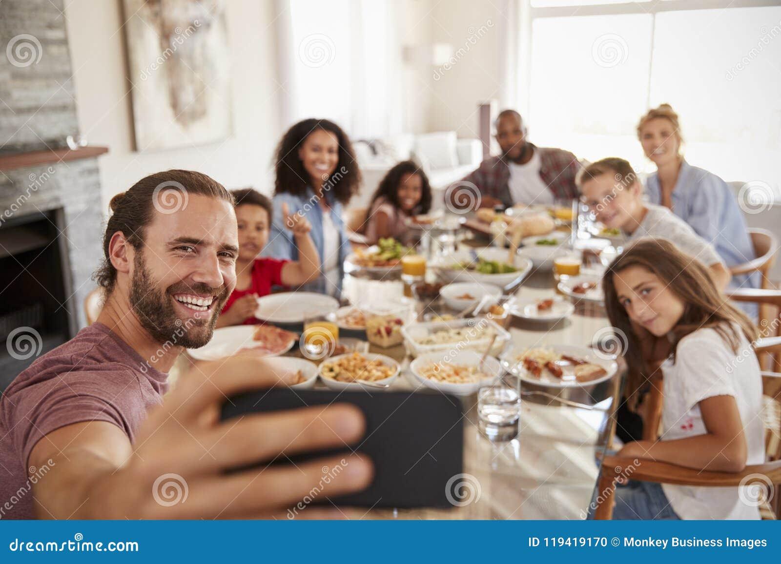 Deux familles prenant Selfie comme elles apprécient le repas à la maison ensemble