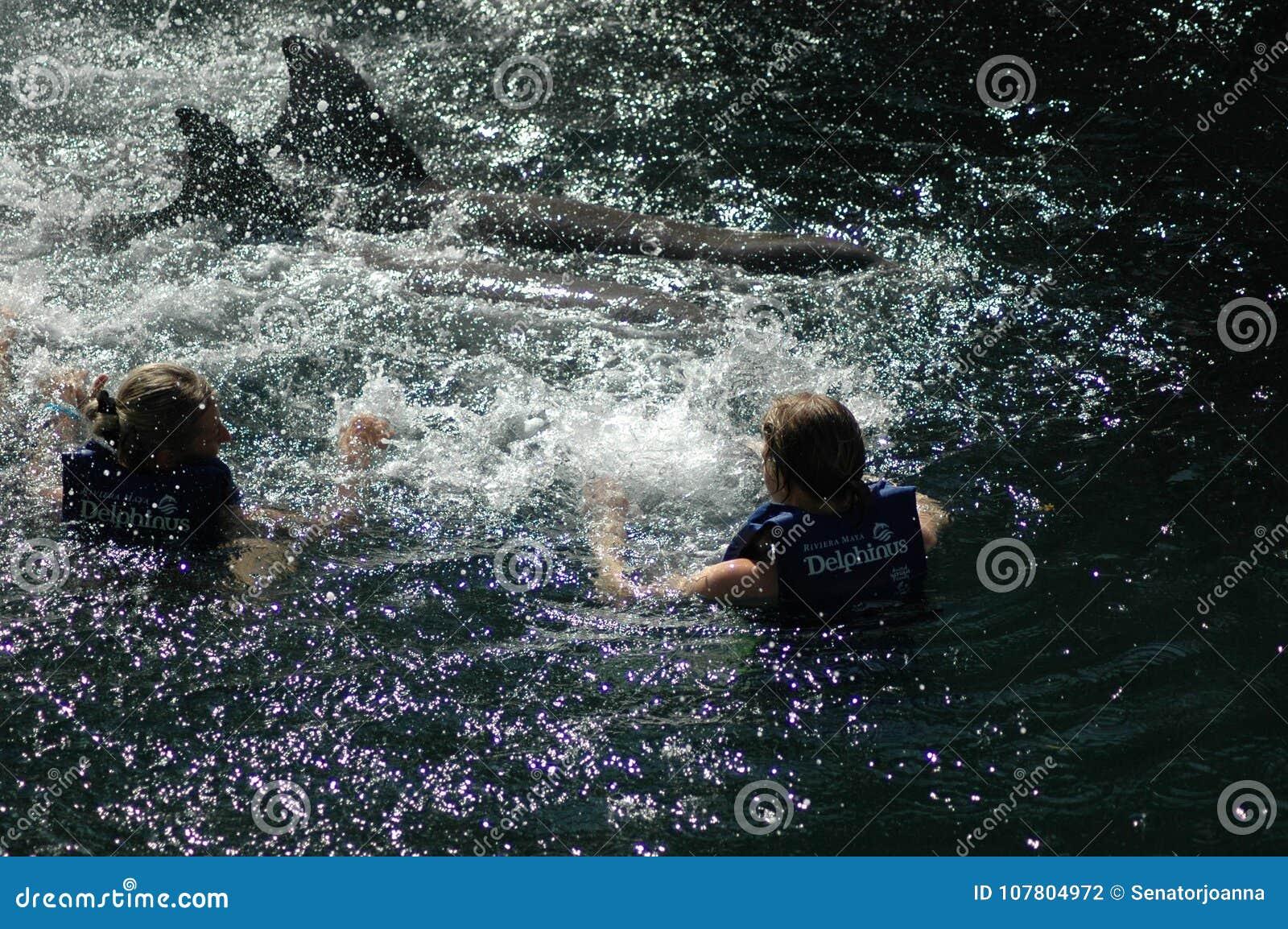 Deux femmes avec deux dauphins au Mexique