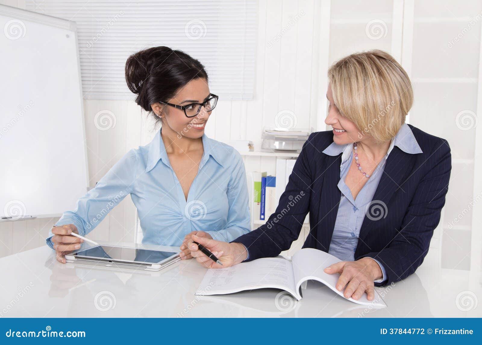 Deux femmes d 39 affaires travaillant ensemble au bureau au bureau photographie stock image for Photos gratuites travail bureau