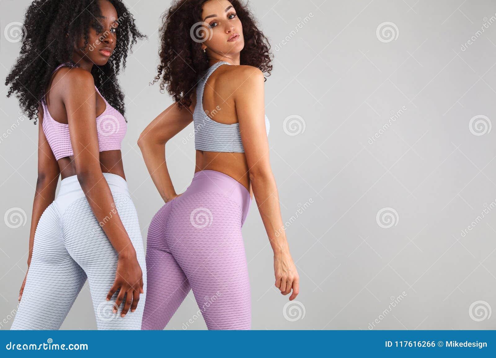 Deux femmes de forme physique dans les vêtements de sport d isolement au-dessus du fond gris Concept de sport et de mode avec l e