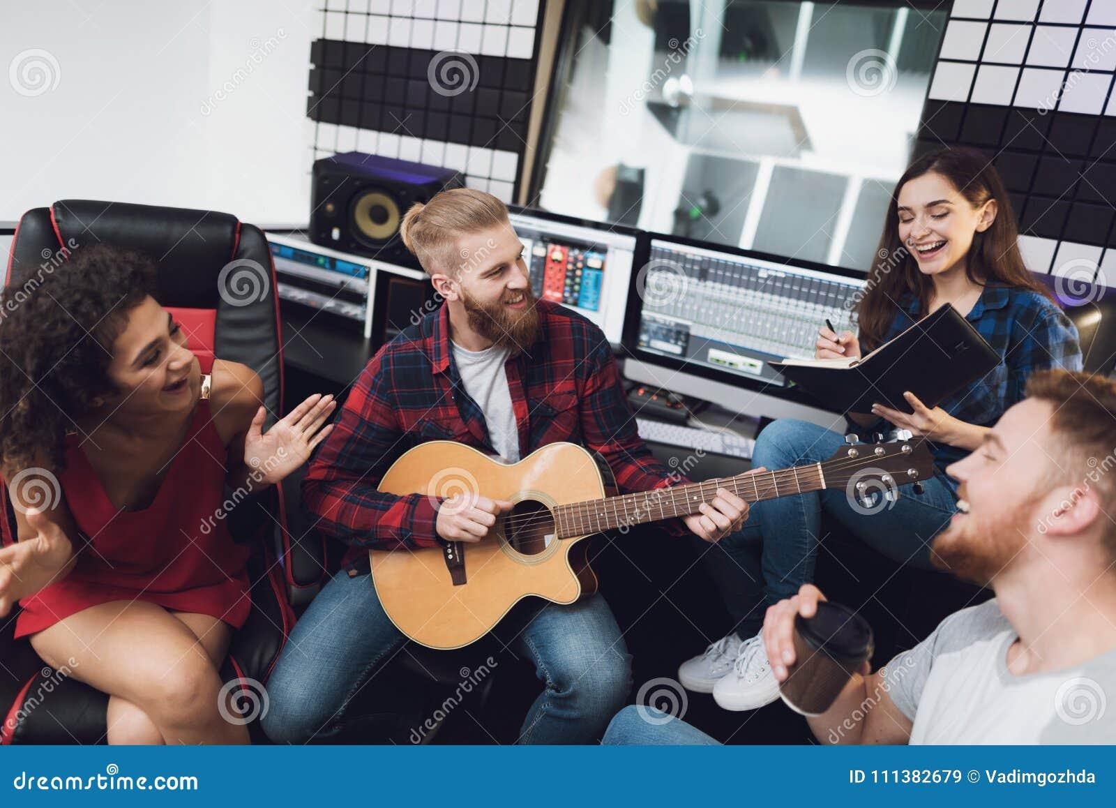 Deux femmes et deux hommes chantent une chanson dans une guitare dans un studio d enregistrement moderne