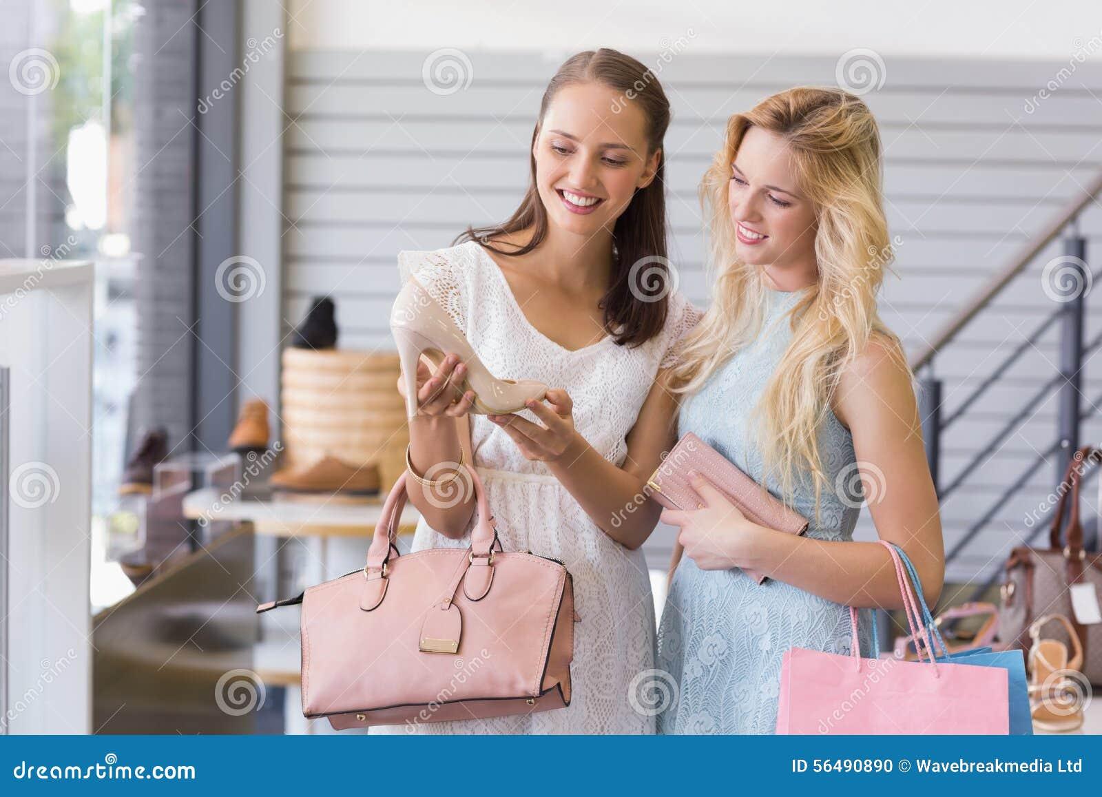 Deux femmes heureuses regardant la chaussure de talon