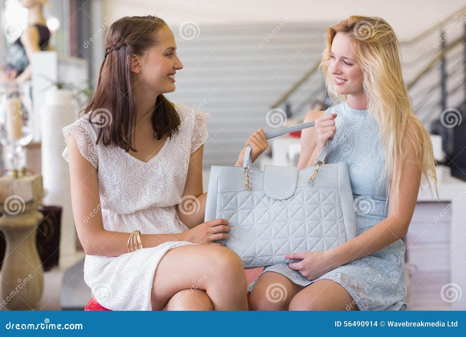 Deux femmes heureuses tenant un sac à main