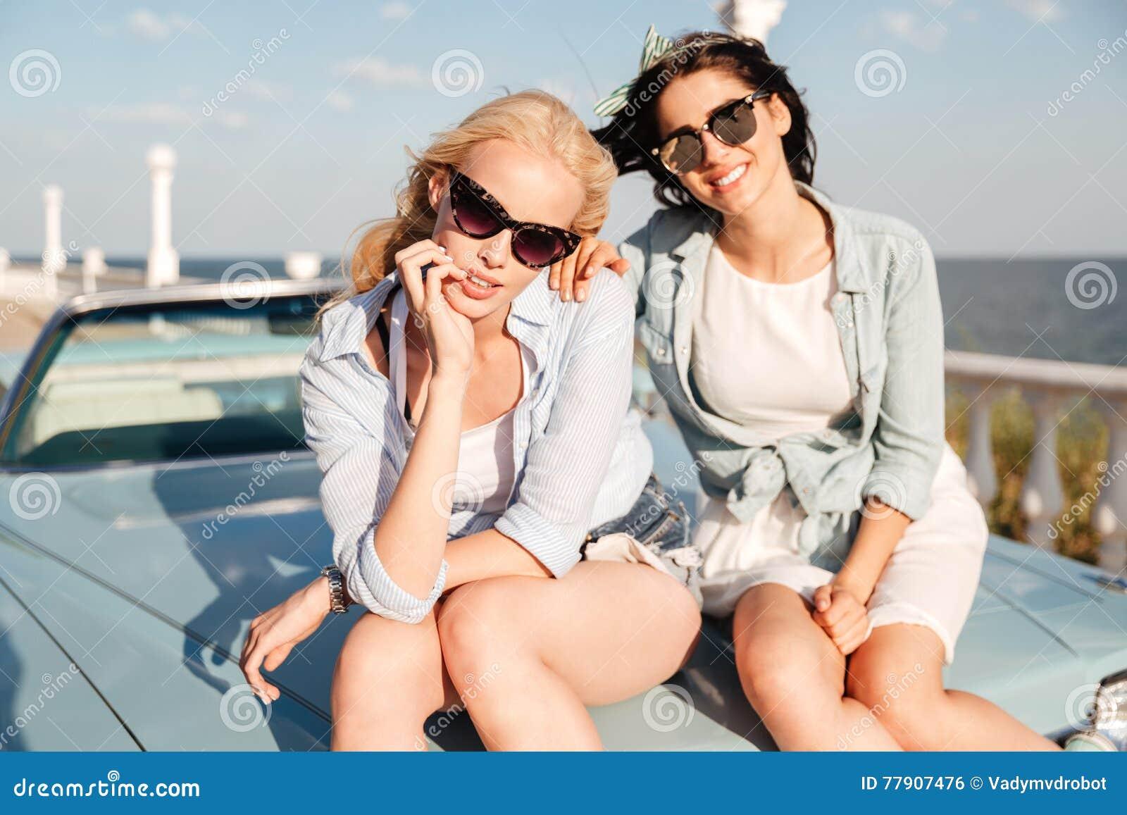 Deux femmes s asseyant sur le capot de voiture ensemble