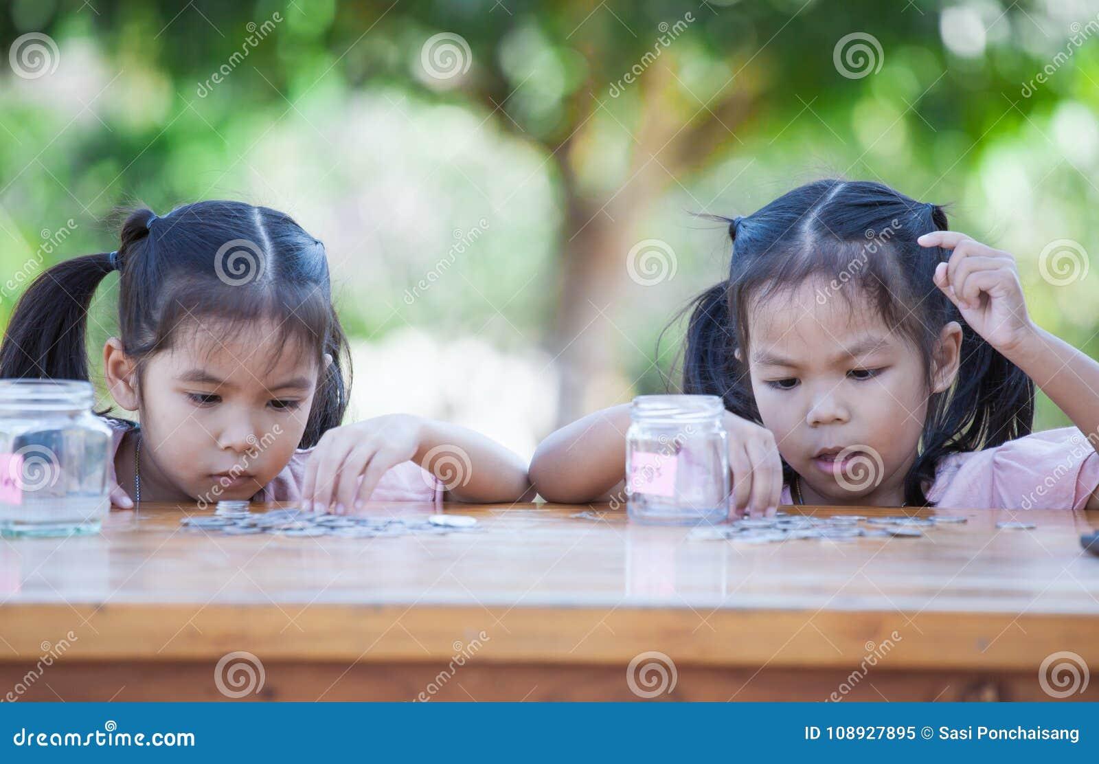 Deux filles asiatiques d enfant comptant et mettant la pièce de monnaie dans la bouteille