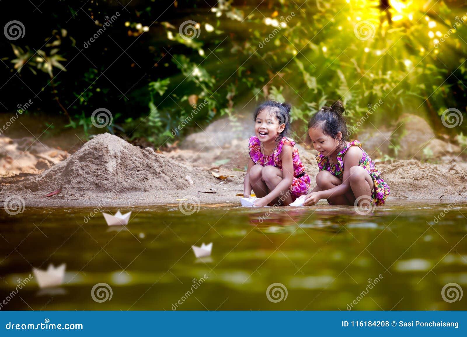 Deux filles asiatiques de petit enfant jouant le bateau de papier dans la rive