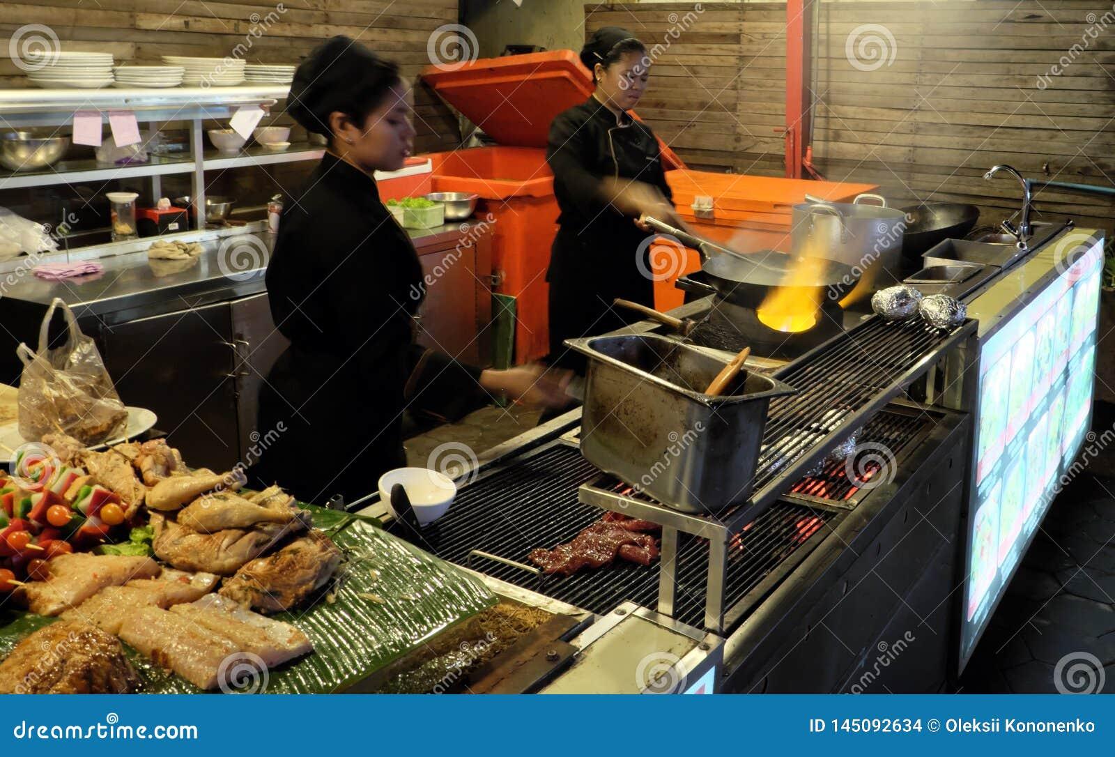 Deux filles asiatiques préparent la nourriture, café de nourriture de rue