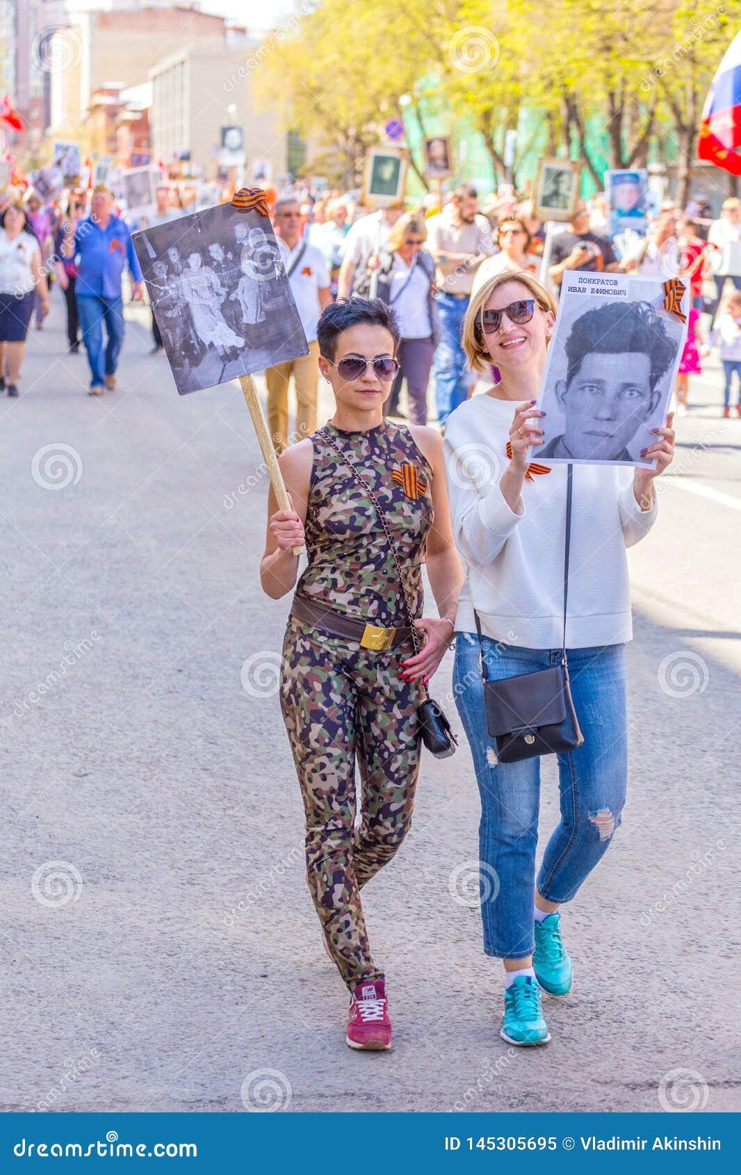 """Deux filles avec des portraits de leurs ancêtres dans l action """"régiment immortel """""""
