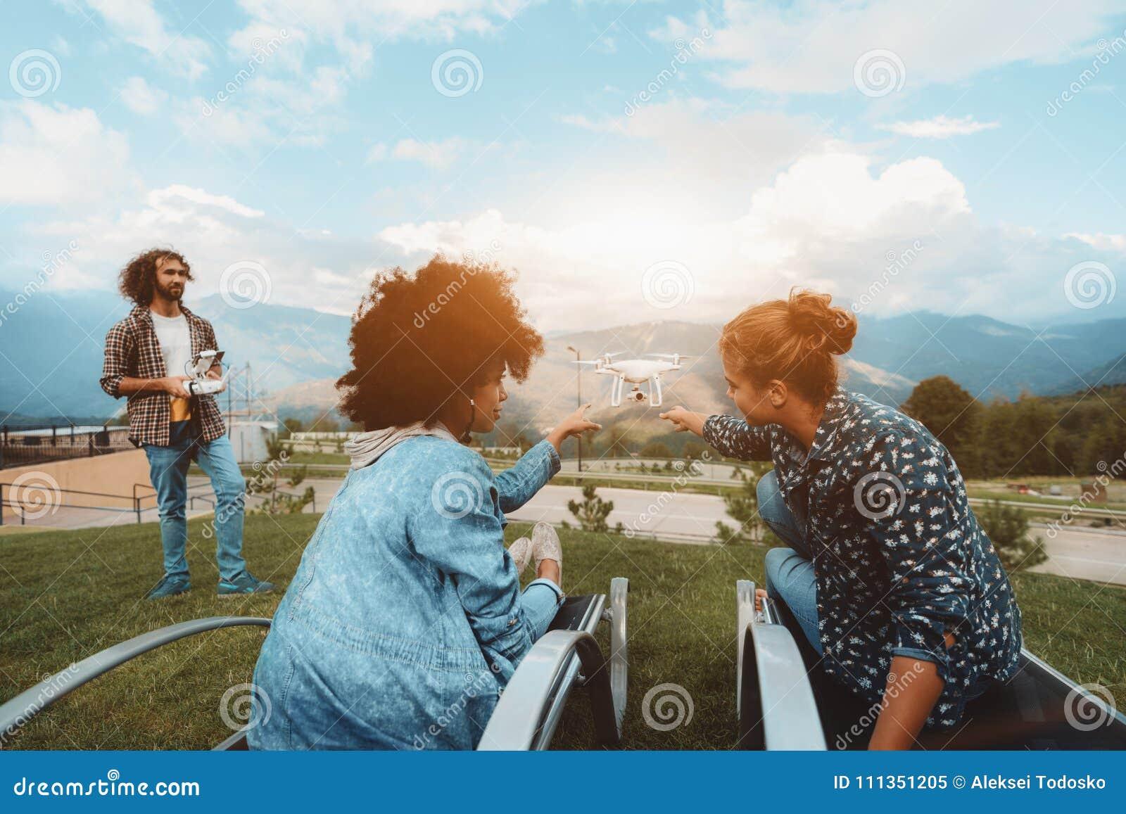 Deux filles, bourdon volant les filmant, opérateur masculin, montagnes b