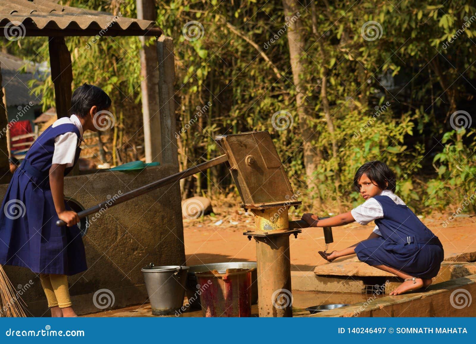Deux filles d école primaire lavent leur main et leurs plats avant de prendre le repas de midi dans une école primaire du Bengale