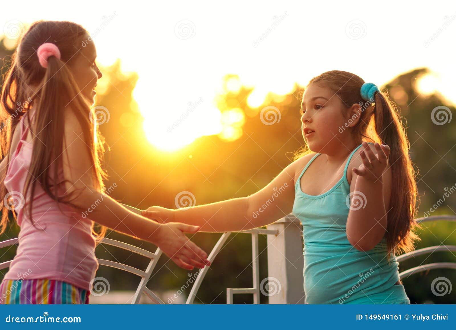 Deux filles d amies parlant sur la rue au coucher du soleil ?coli?res, deux filles des vacances