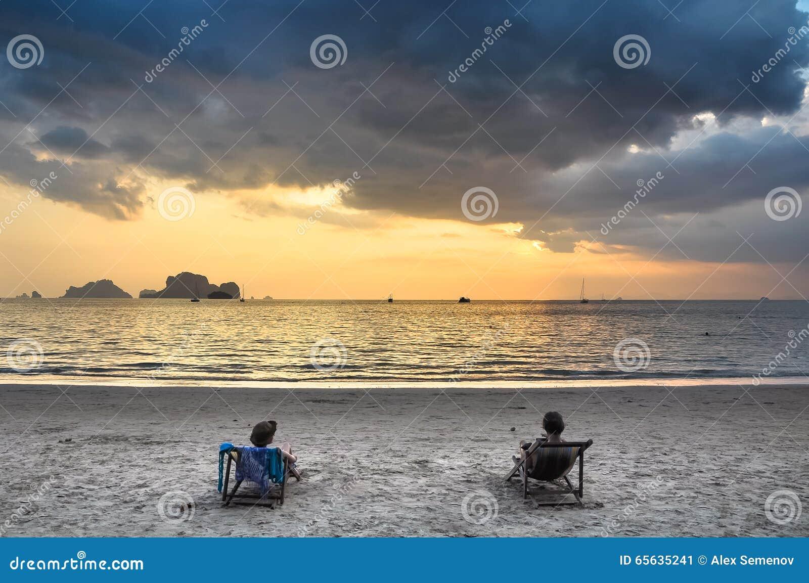 Deux filles dans des chaises de plage admirant le coucher du soleil en mer