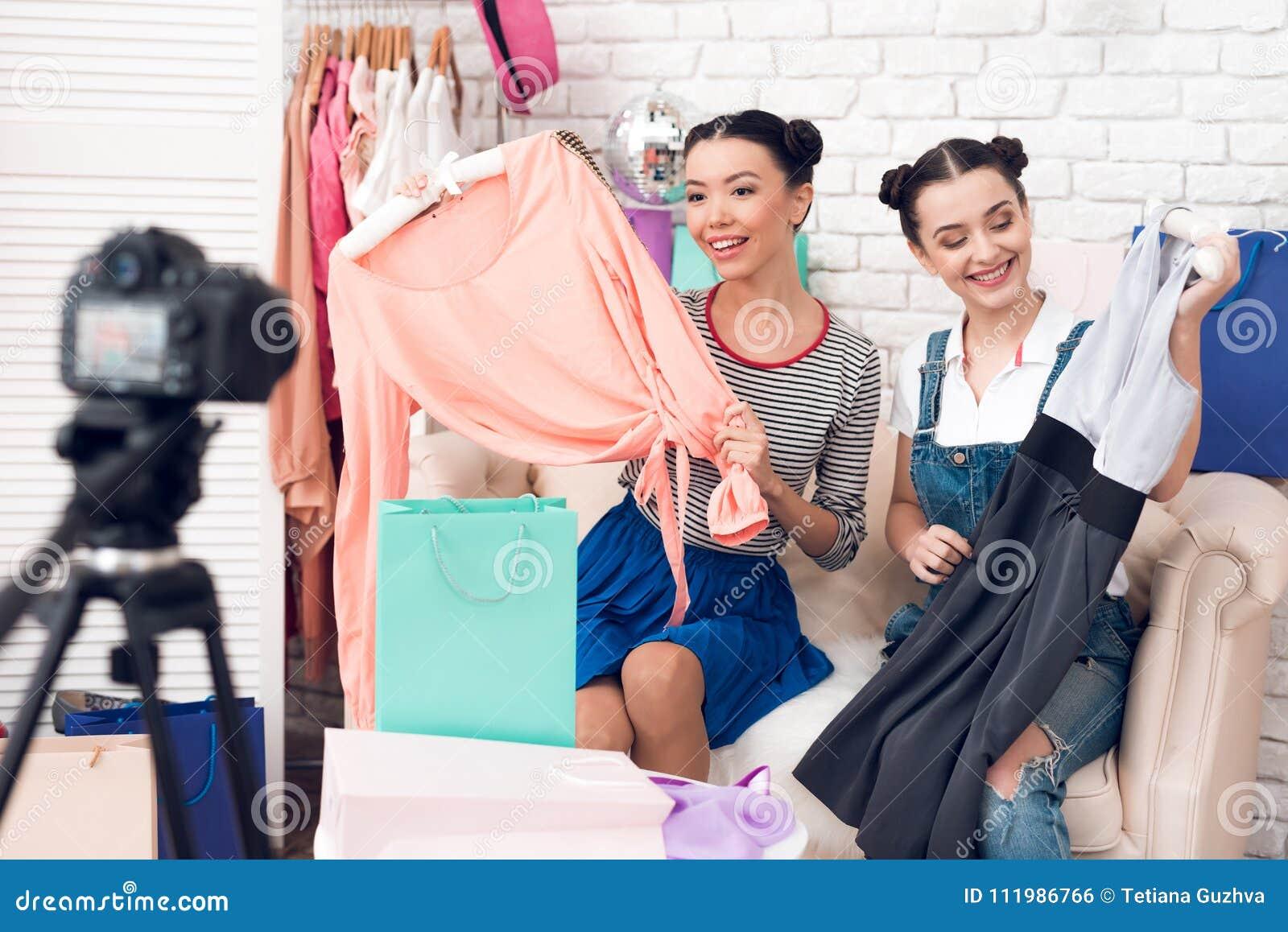 Deux filles de blogger de mode tirent la robe colorée des sacs colorés à l appareil-photo