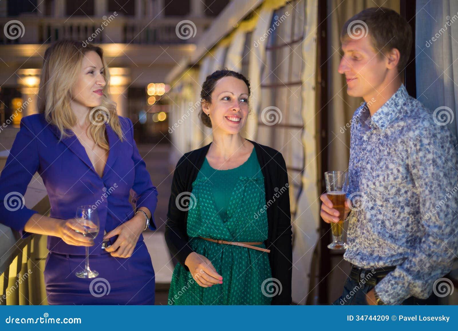 Deux filles et un type se tenant avec un verre