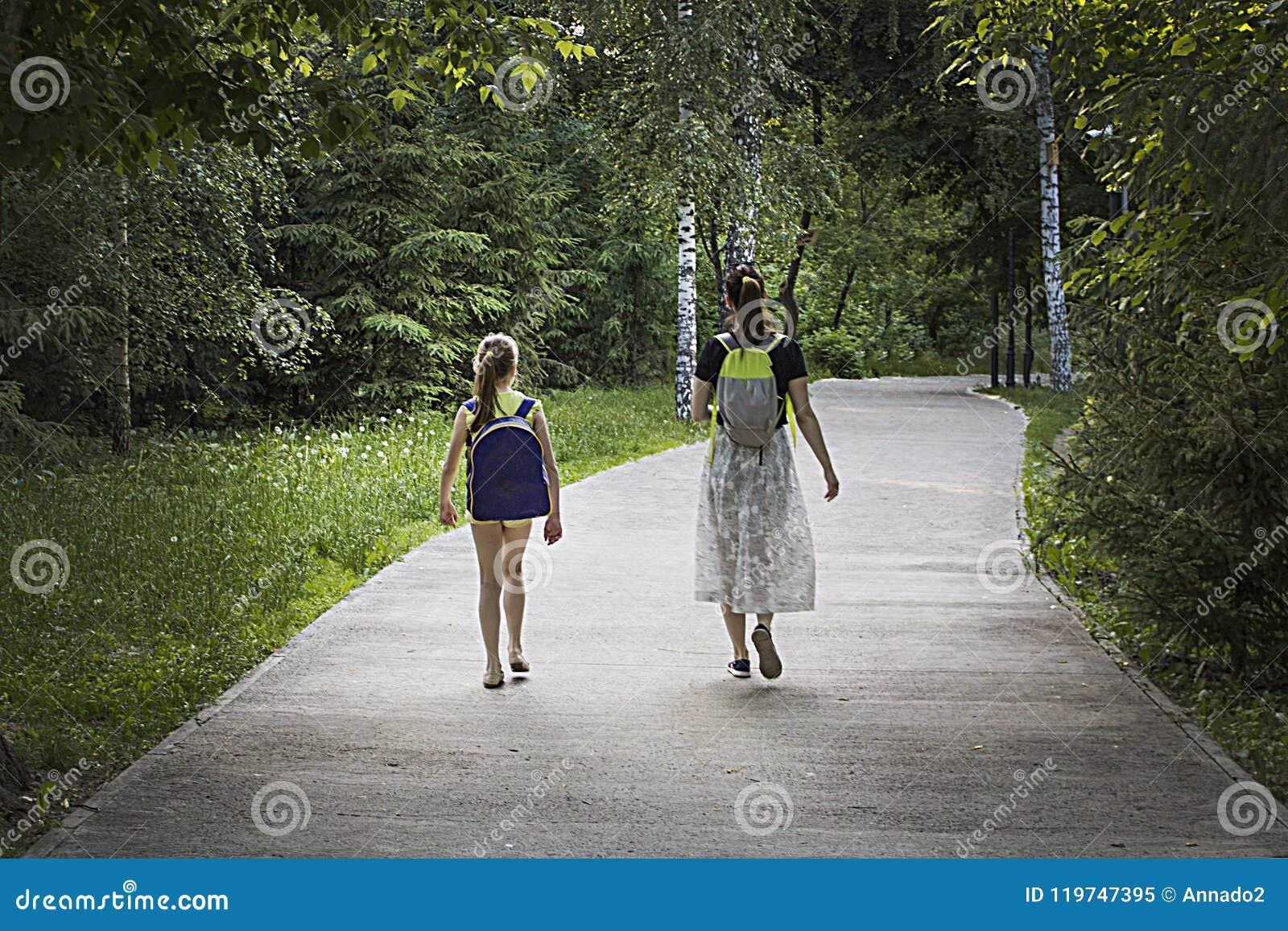 Deux filles marchent en parc avec des sacs à dos