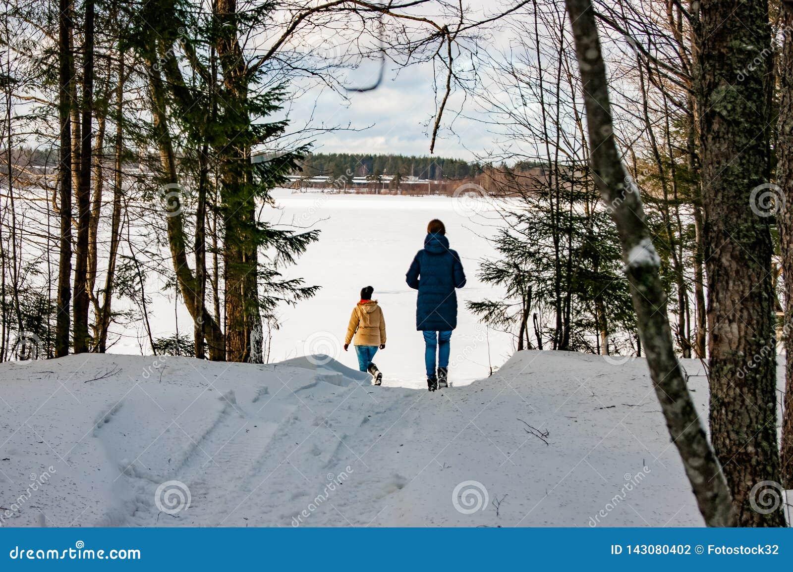 Deux filles marchent par la forêt d hiver au lac