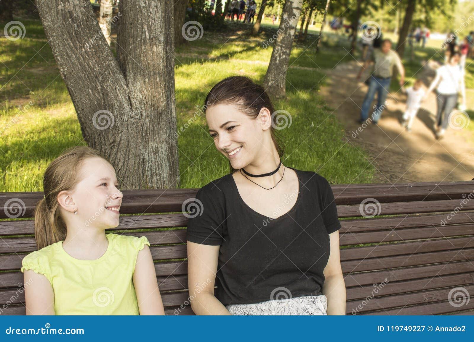 Deux filles s asseyent sur un banc parlant et riant