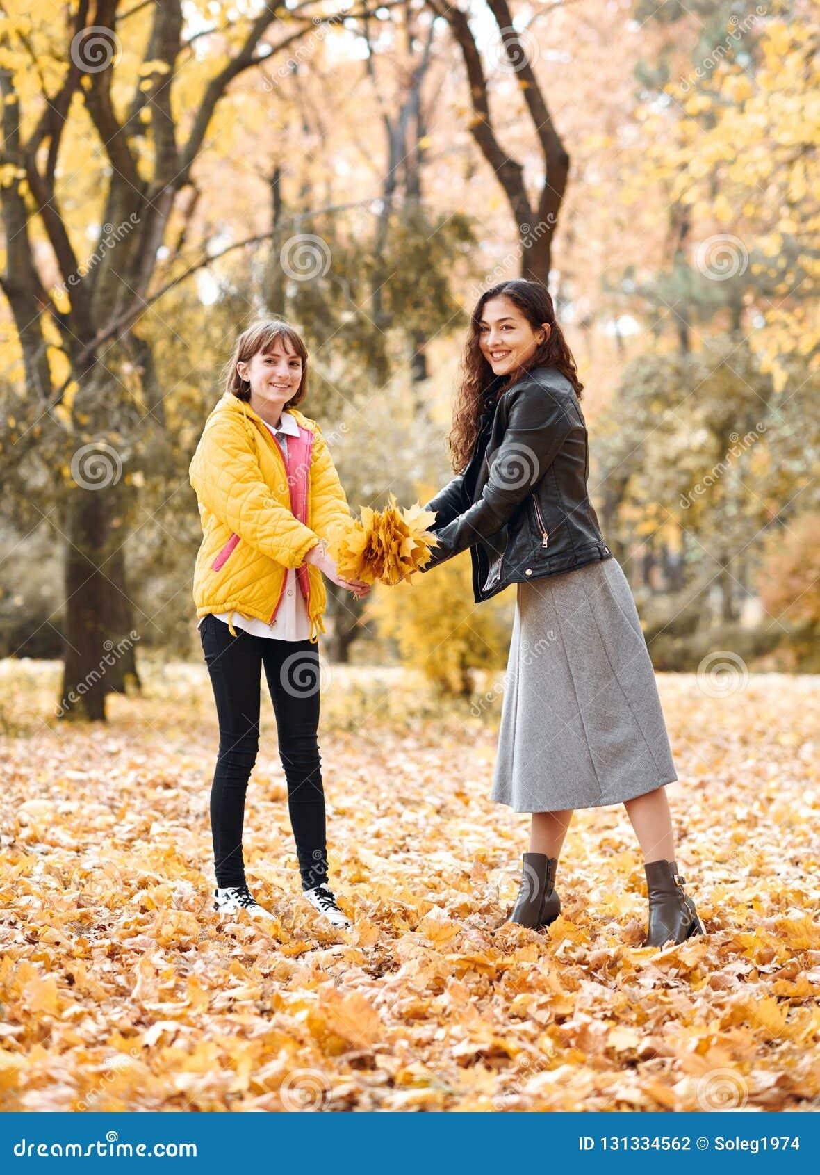 Deux filles sont en parc de ville d automne Ils sélectionnent des feuilles