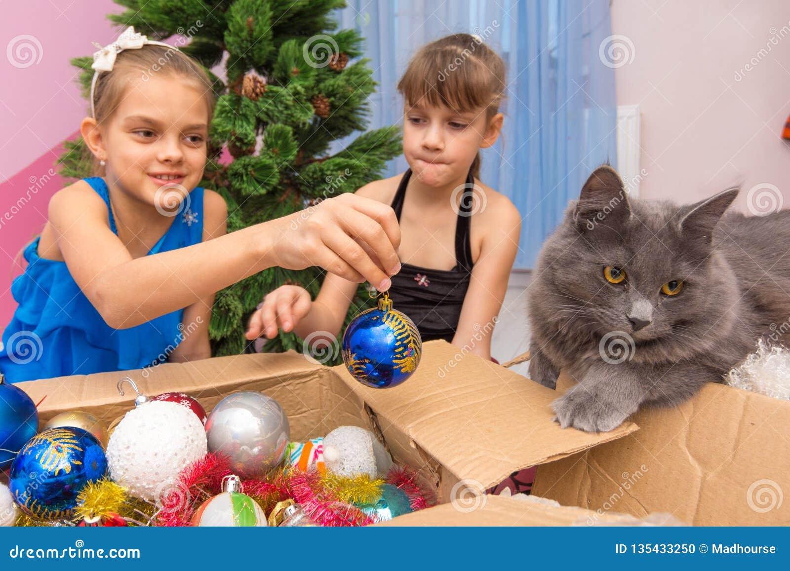 Deux filles tirent des jouets de Noël hors de la boîte et montrent le chat