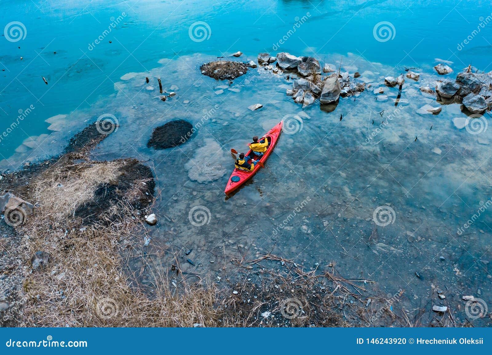 Deux flotteurs sportifs d homme sur un bateau rouge en rivi?re